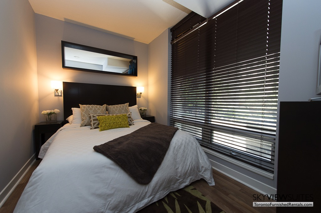 8 Colborne Street short term rental toronto bedroom with green pillow and shuttered windows