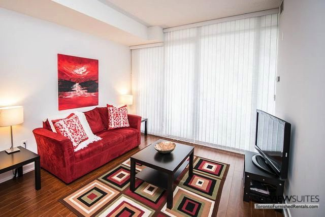 8 Telegram Mews serviced apartments toronto red couch and rug