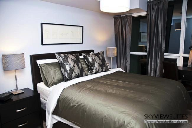 furnished suites toronto harbourfront bedroom with grey sheets and desk