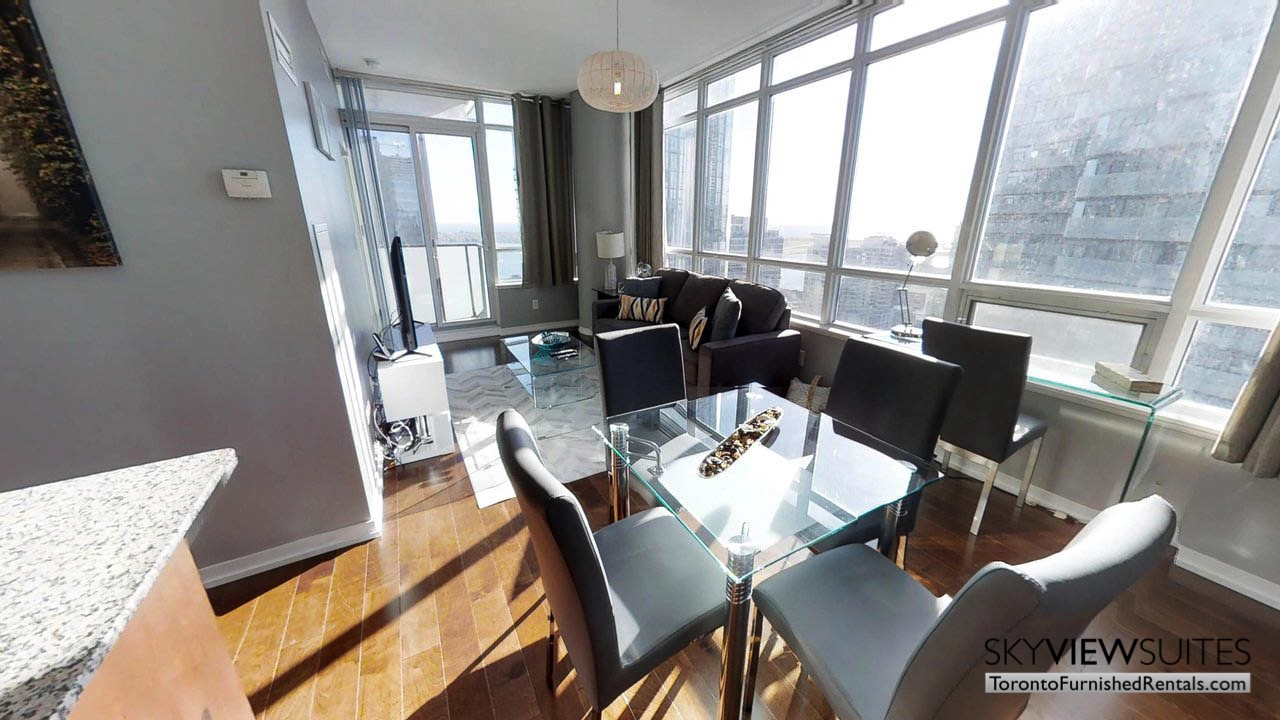 furnished rentals toronto Maple Leaf Square living room with dining area and skyline view