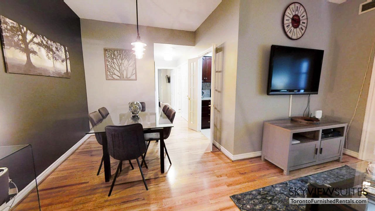 short term rentals toronto qwest living room with dining table and wall-mounted television
