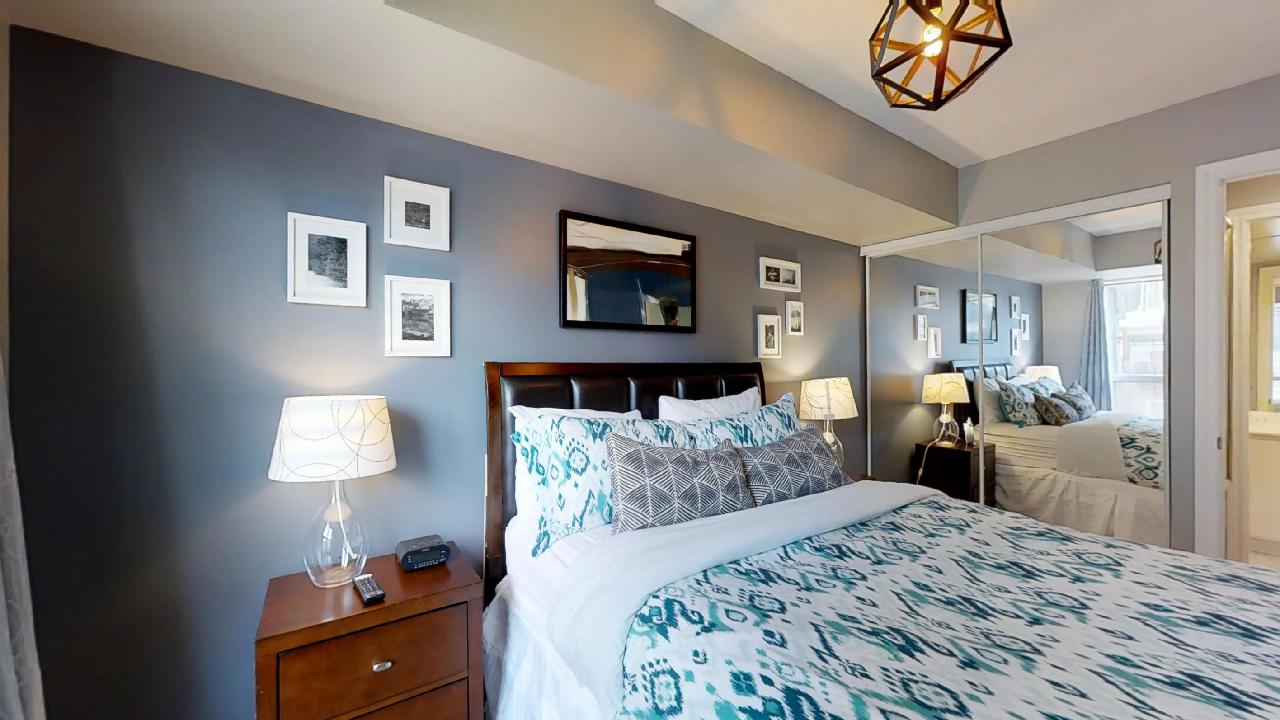 master bedroom with blue sheets in furnished apartment near queen and university Toronto
