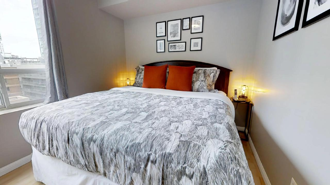 bedroom with red pillows at simcoe and richmond toronto funished apartment