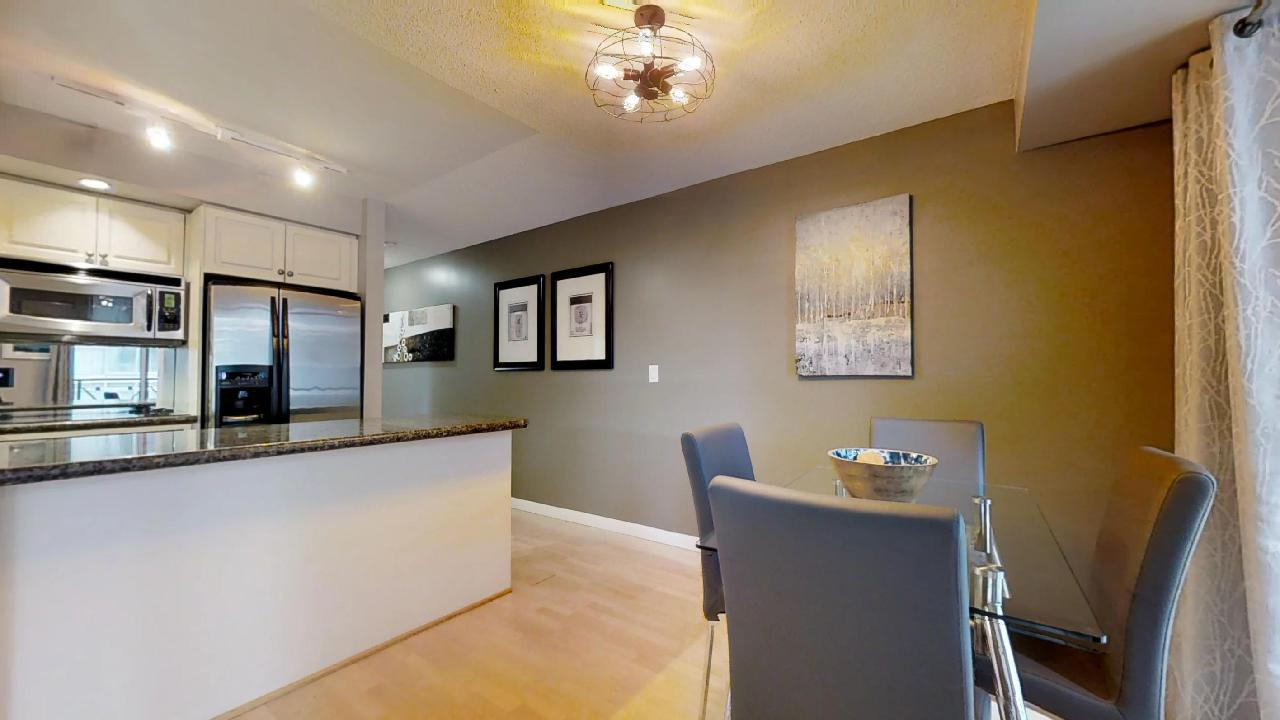dining area and kitchen with art on the walls in a furnished apartment in downtown toronto