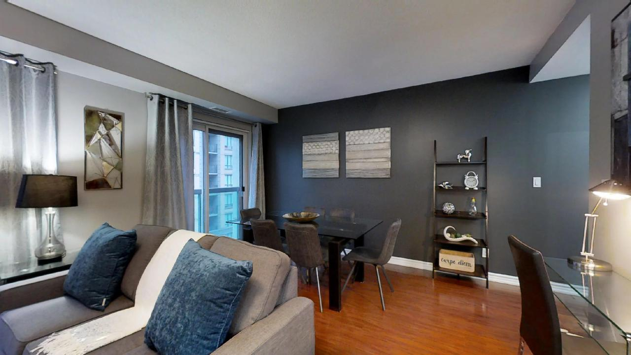 the living room and dining area in a toronto furnished apartment, featuring gray walls and a blue pillow