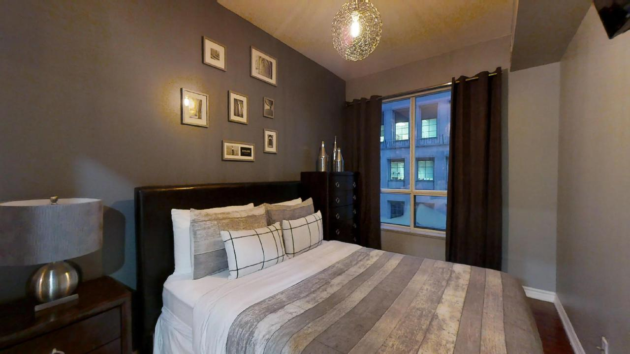 A bed featuring grey sheets in a furnished unit in Toronto, near the Entertainment district