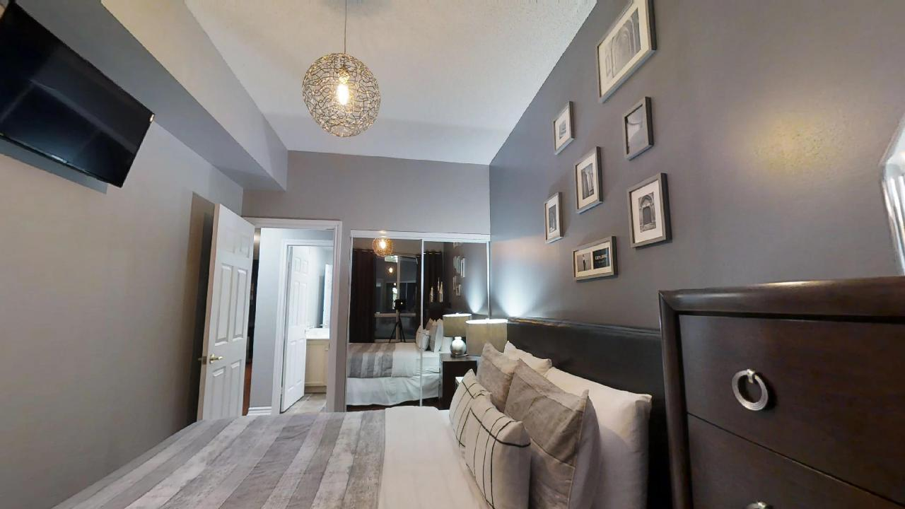 a bedroom and mirror, with a ceiling light, in a furnished apartment in Toronto located at 168 simcoe street