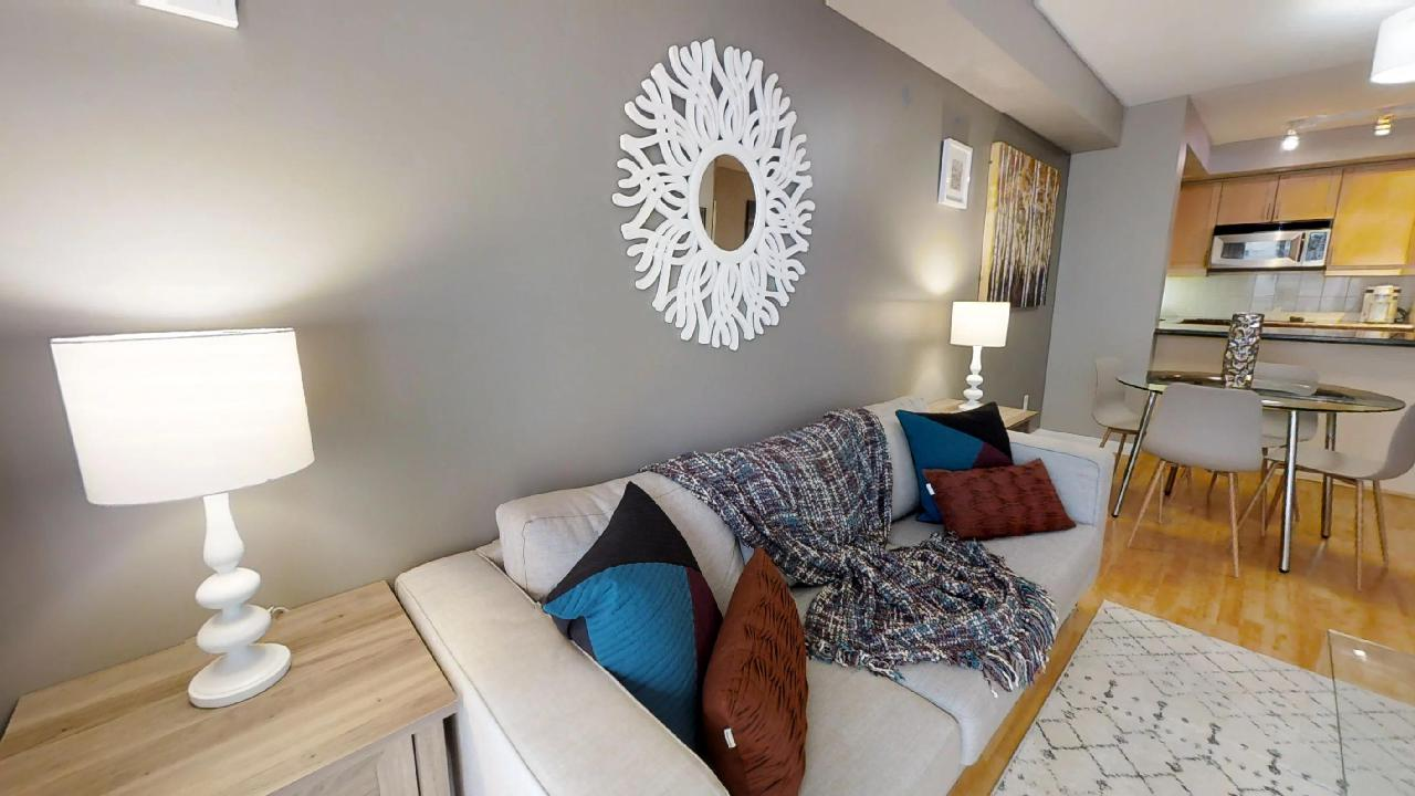 Wall decoration and couch with pillows in a toronto furnished unit near queen and simcoe, toronto
