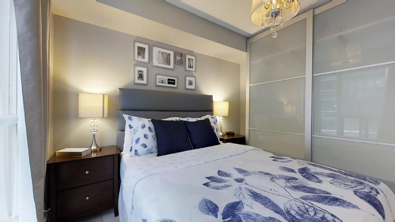 a blue bed with wall art in a toronto furnished apartment