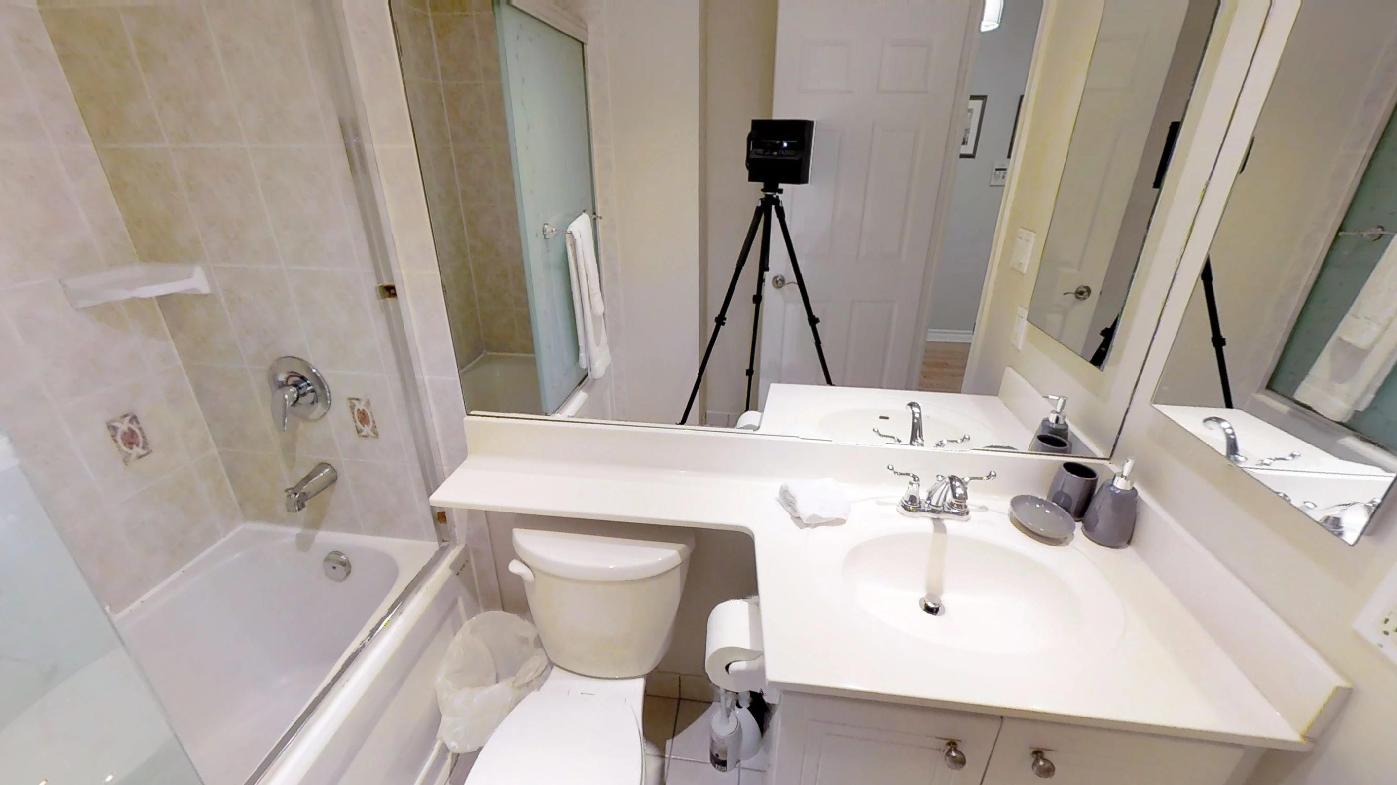 a view of the shower, countertop and toilet in the furnished bathroom of Icon G, near the CN tower in downtown Toronto.