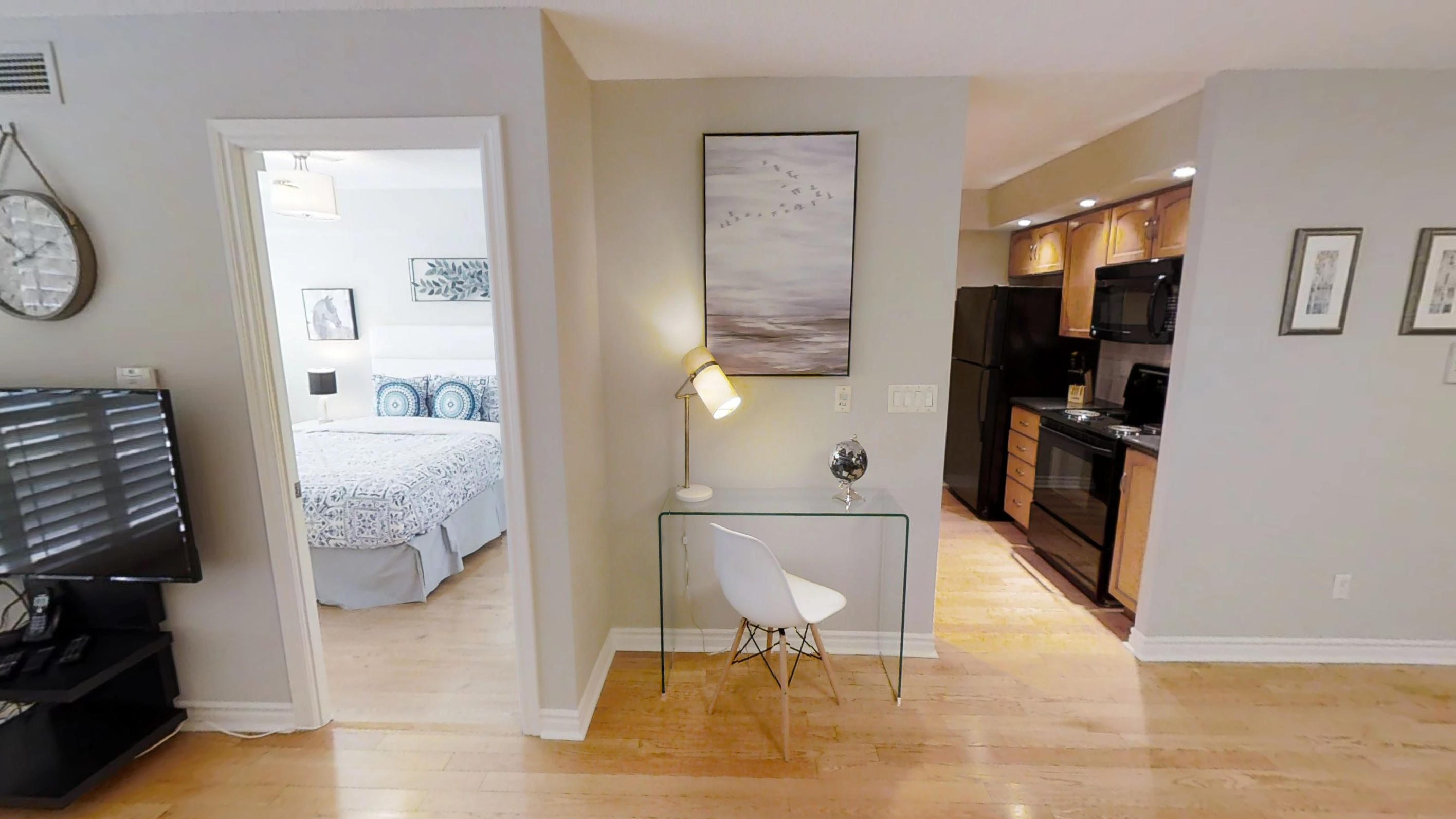 the glass desk and view to the bedroom in a one bedroom toronto furnished apartment near blue jays way and wellington streets