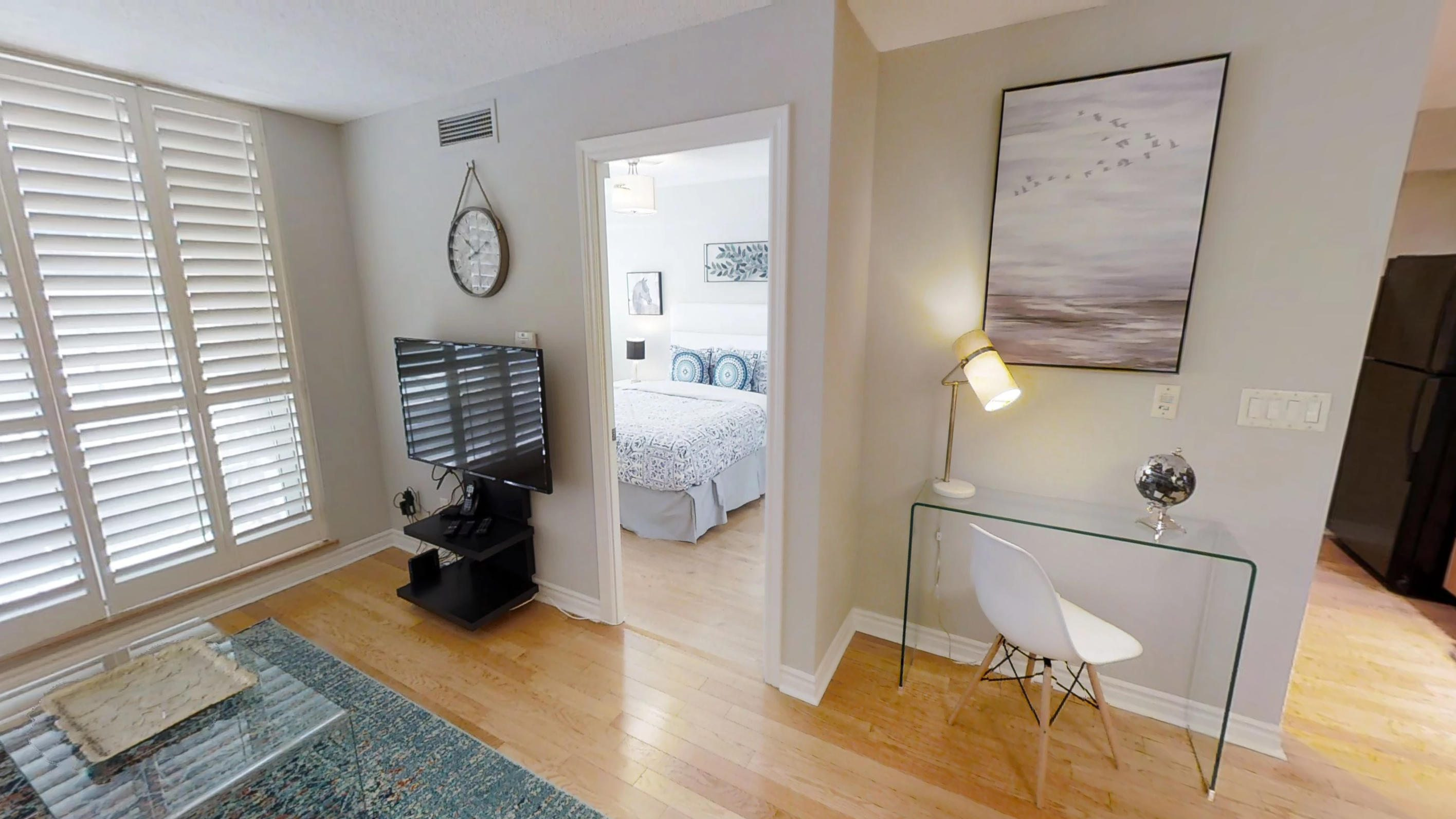 the television and bedroom in a furnished one bedroom toronto apartment, near wellington and john street