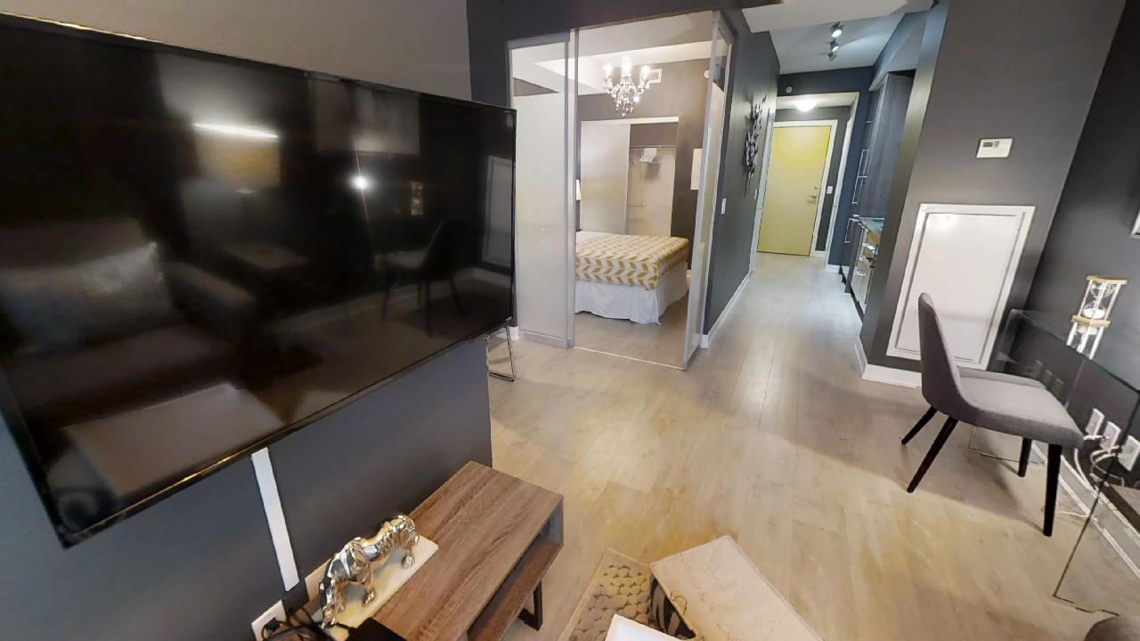 view of the bedroom and front hall of a furnished apartment, in the entertainment district of toronto