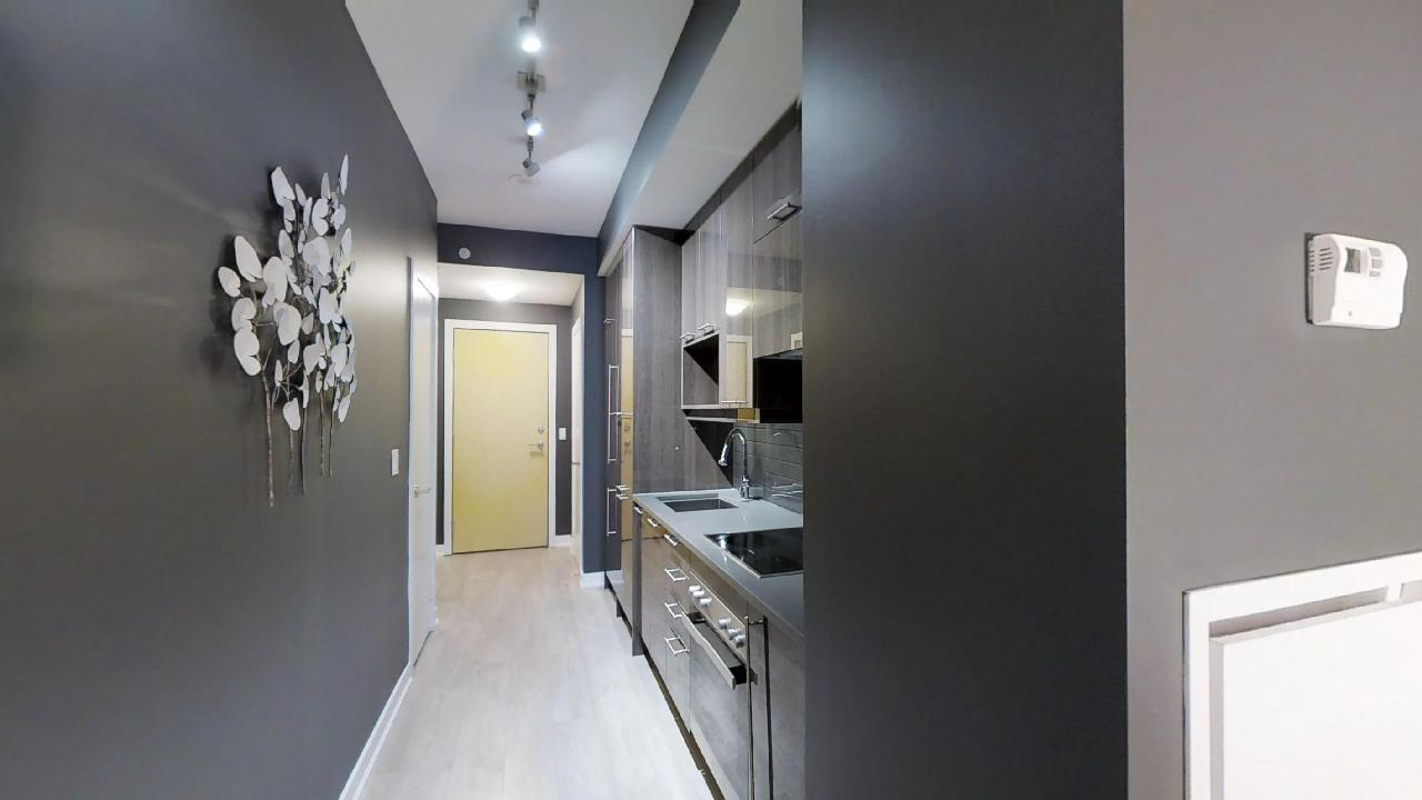 a yellow door and front hallway in a toronto furnished apartment