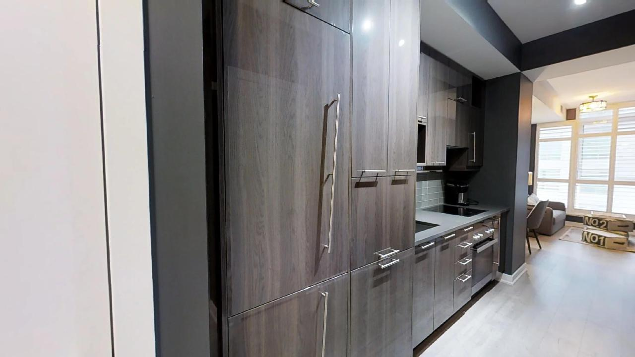 the wooden door to a fridge in a toronto furnished apartment