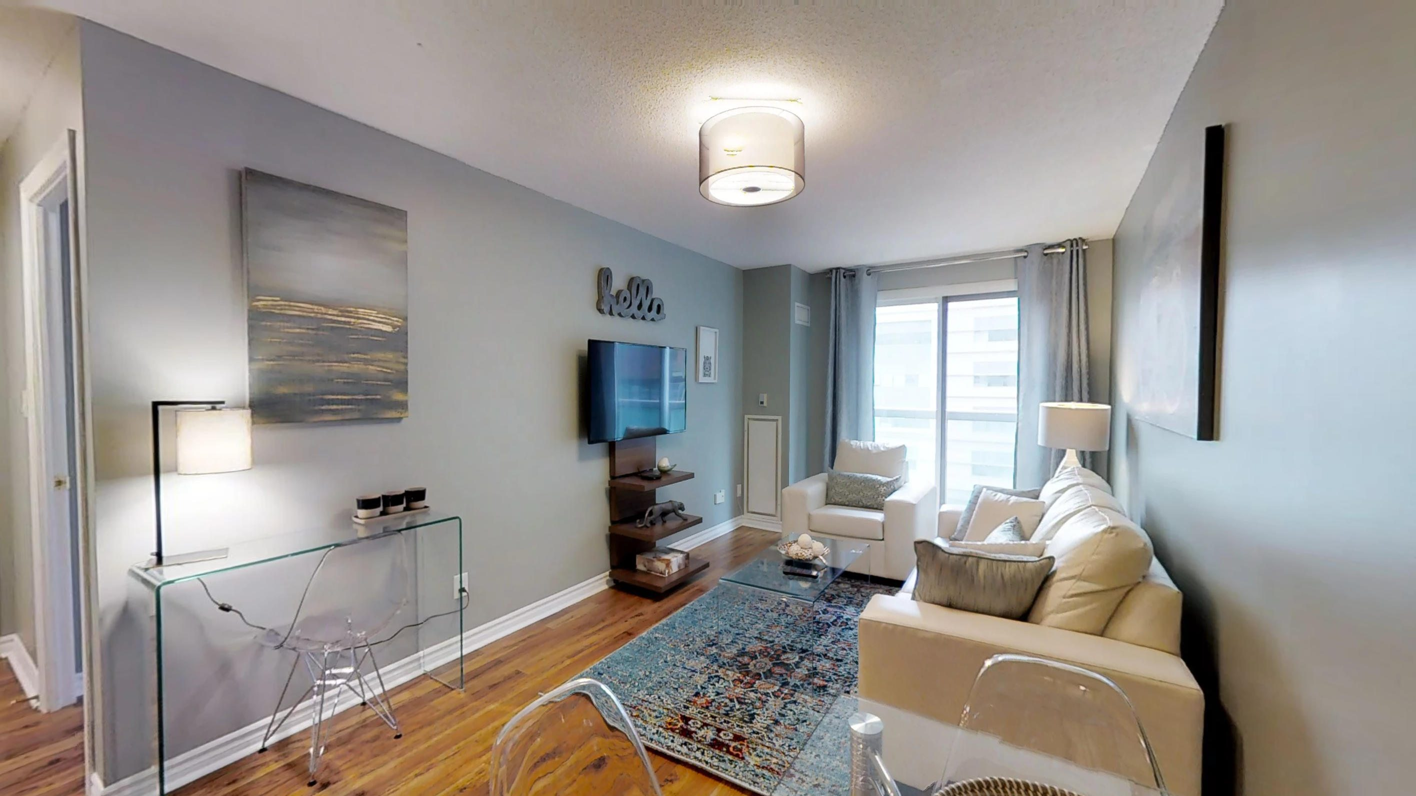 rugs, wall art, and window in the living room of a furnished apartment in Toronto's Financial District