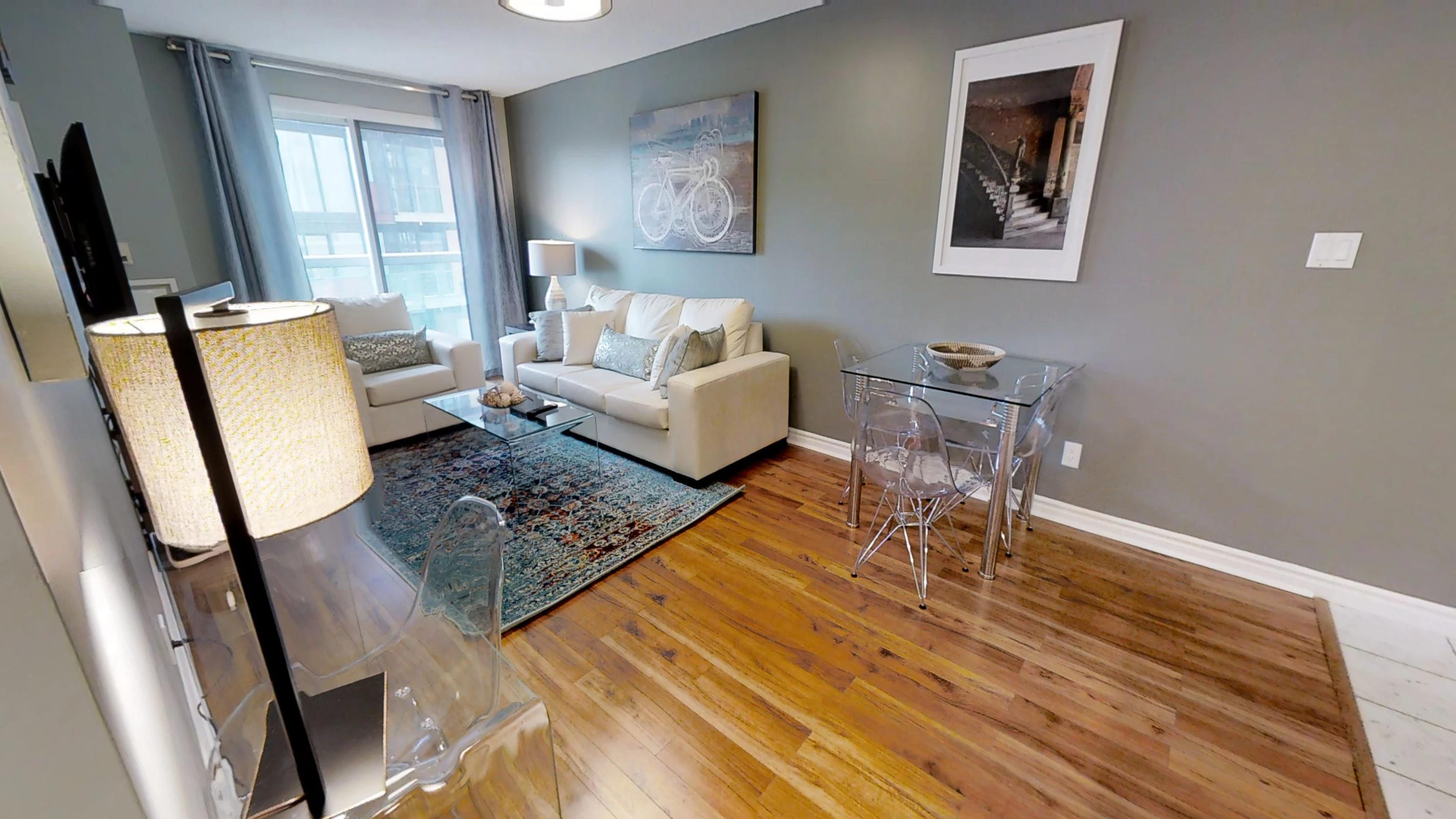 the main living space of a Sky View Suites toronto furnished apartment, located at Qwest condos on 168 simcoe street