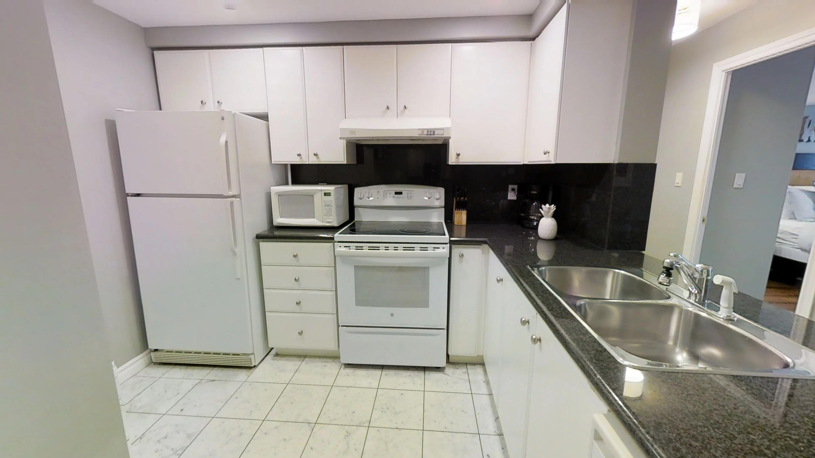 The fully furnished kitchen in a Qwest condominium, furnished by Sky View Suites in downtown Toronto.